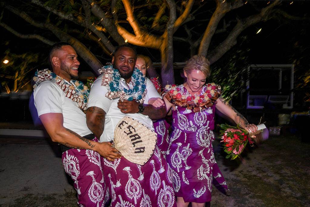 The bridal party in traditional Fiji skirts dance with the bride's customised fan