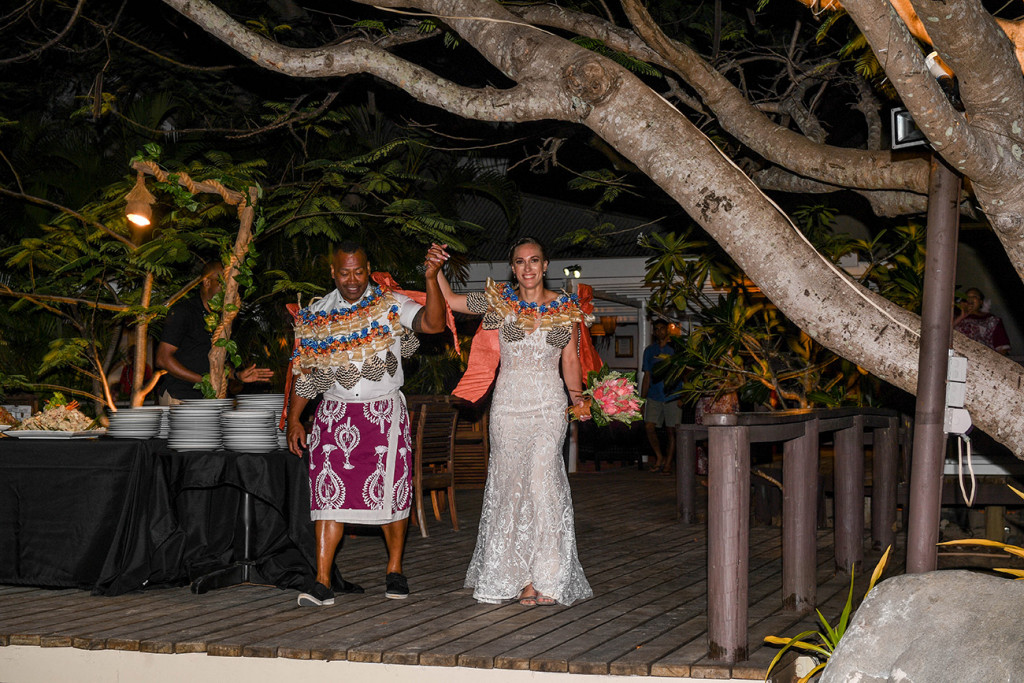 The newly married Fiji bride and groom arrive at the reception venue holding hands