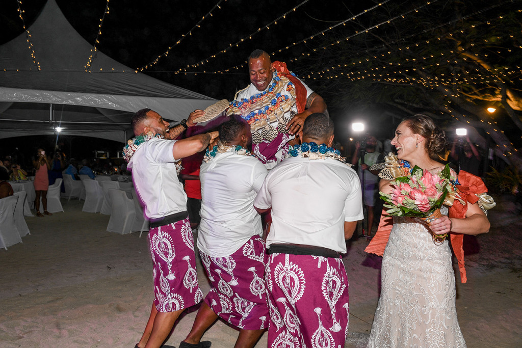 The groom laughs as the groomsmen lift him into the air against the fairy lights