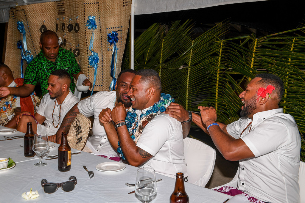 The groomsmen chat and laugh while seated at the wedding reception