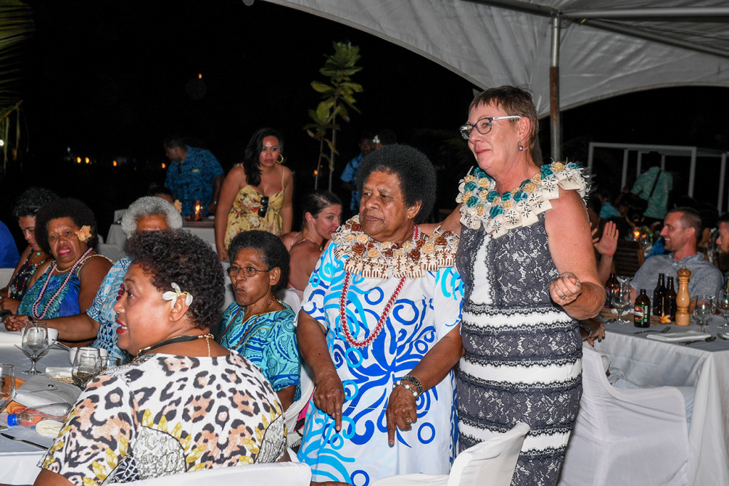 The bride and groom's mothers donned in Fiji flower wreaths stand up and dance during performances