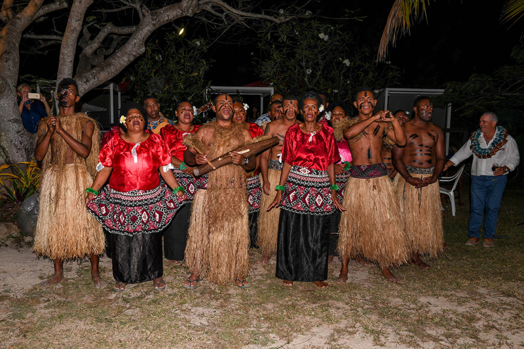 Traditional wedding Fiji meke (dance) performed under fairy lights on the beach