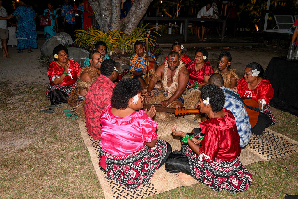 Sitting on a handwoven kivu (mat) as they perform a Fiji meke
