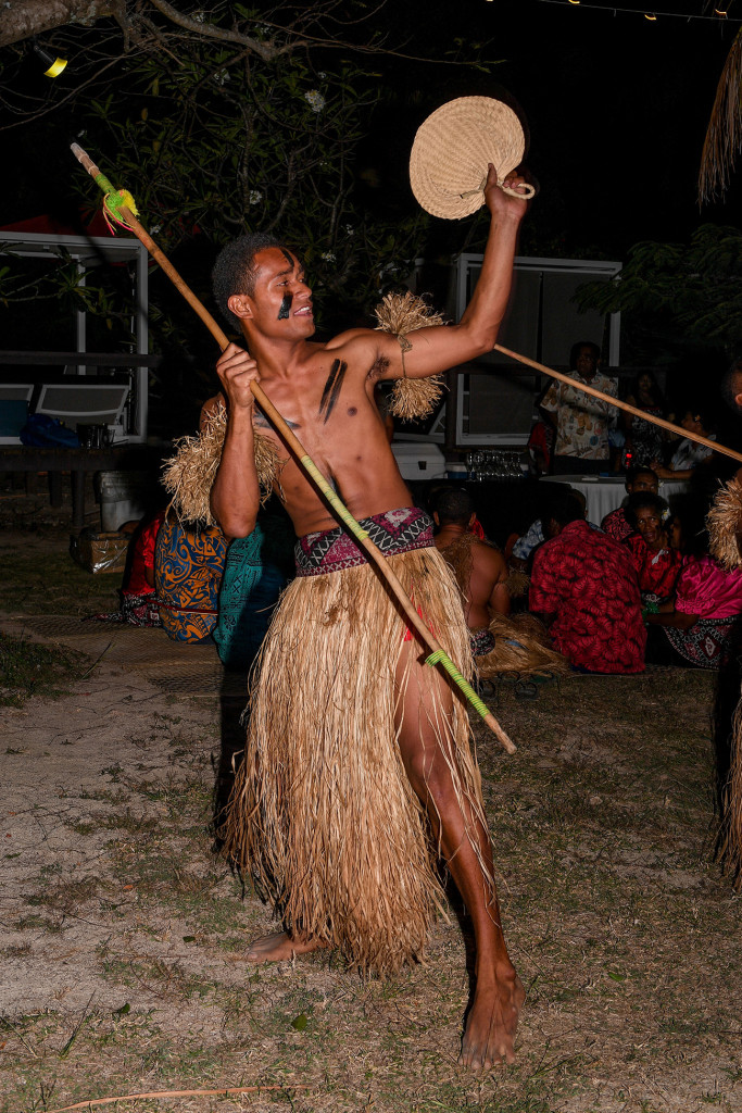 A Fiji warrior dancing with his fan and staff