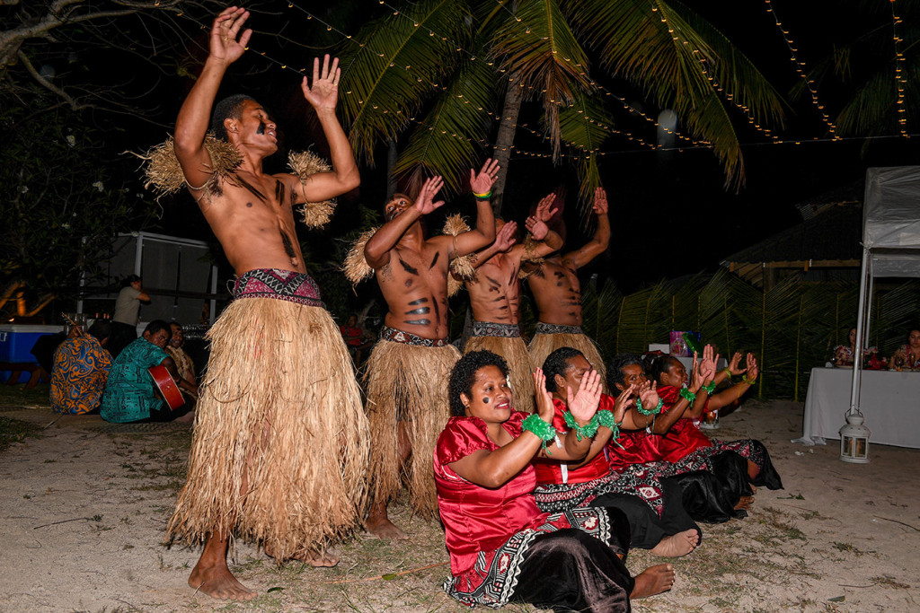Traditional Fiji performers sing and dance on the beach at Musket Cove