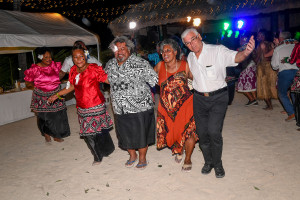 The bride's family joins the traditional performers for a dance on the beach
