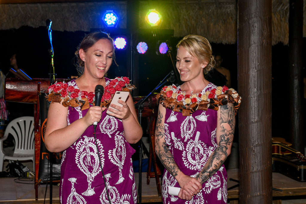 Bestmaid reads her speech from her phone as another bridesmaid watches