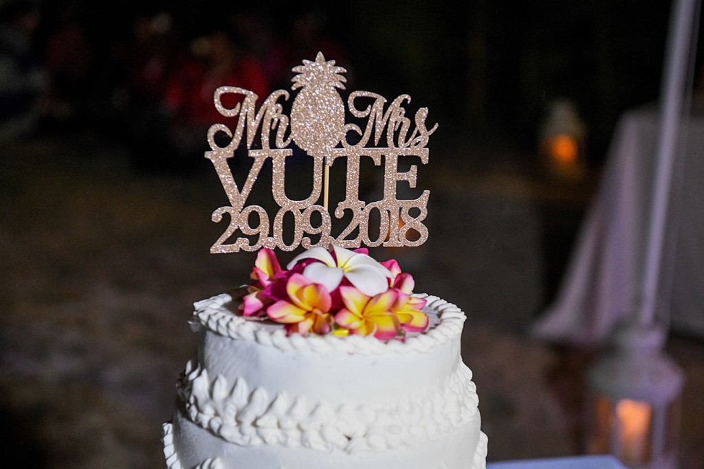Brilliant white cake topped with colourful frangipani flowers with Mr and Mrs Vute topper