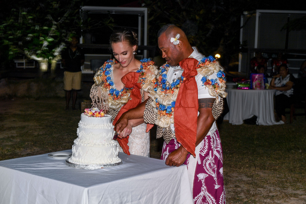 The bride and groom cut the brilliant white cake together