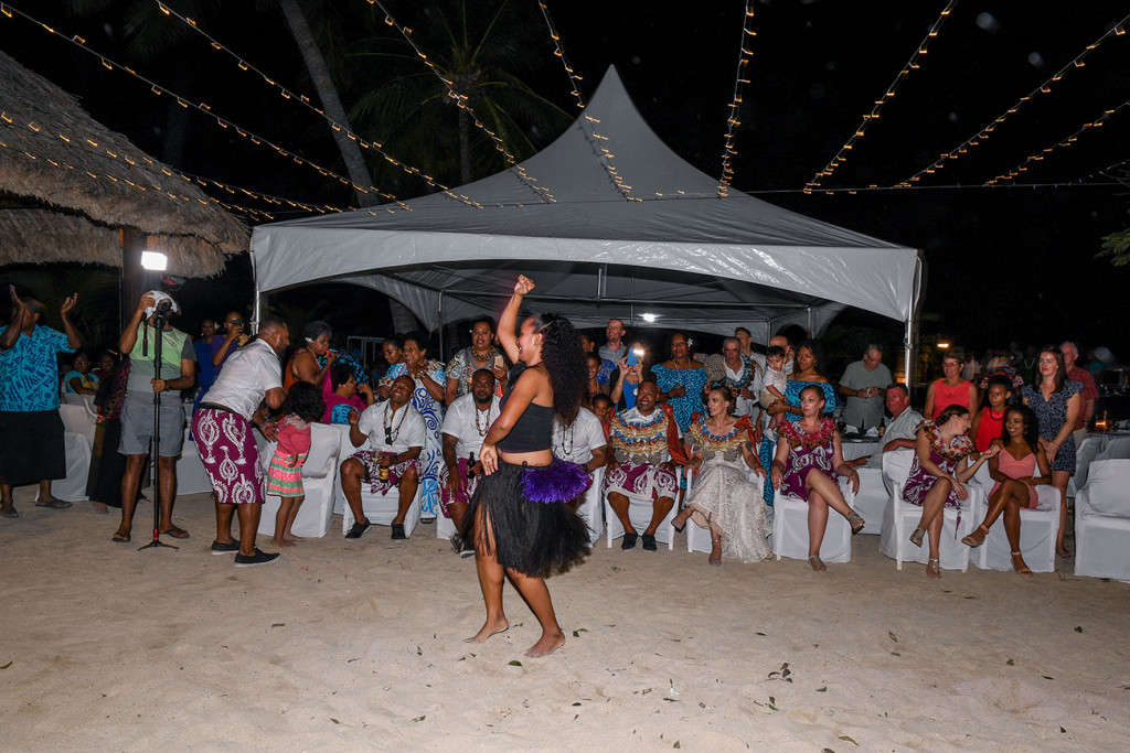 A Fiji dancer wearing black sisal skirt entertains the wedding guests