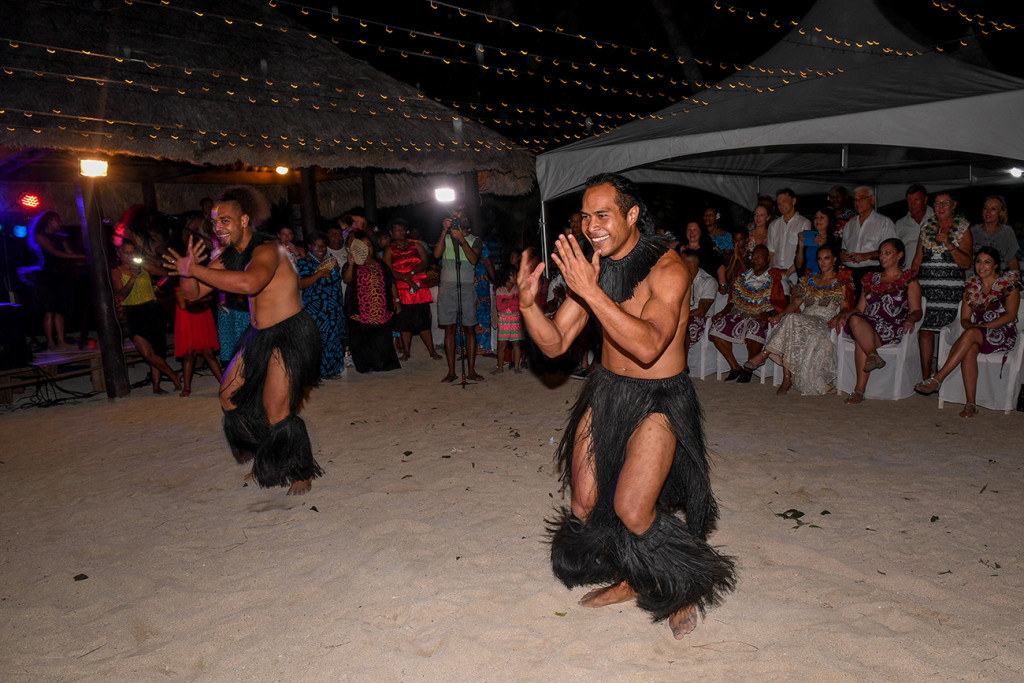 Male performers dressed in black sisal entertain the wedding party