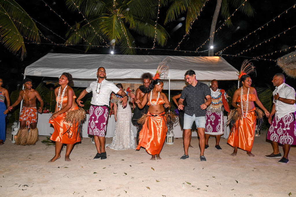 Bridal party join the dancers dressed in orange on the beach dance floor