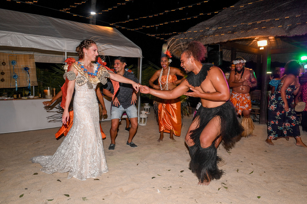 The bride dances with a Fiji performer on the beach at their wedding reception
