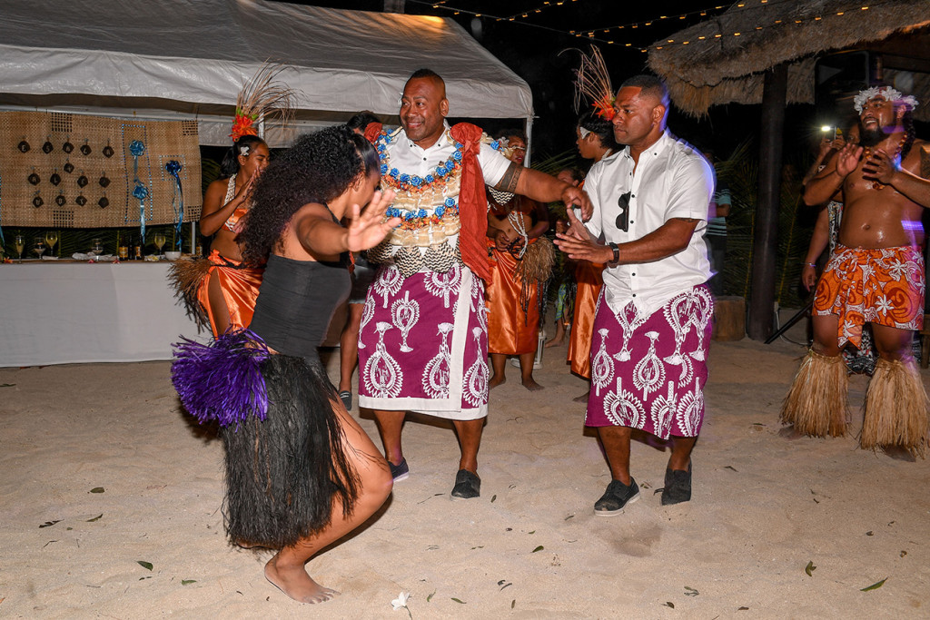 Fiji performer in black and purple sisal skirt dances with groom