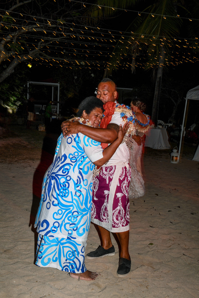 The groom hugs his mother as he dances with her on the beach at Musket Cove Fiji
