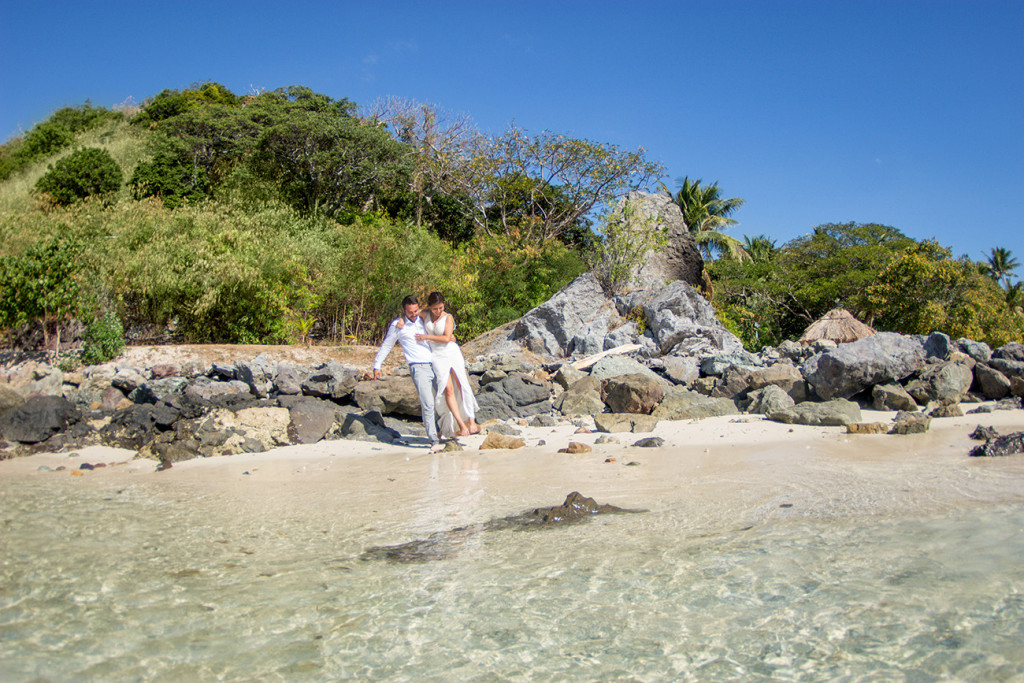 Groom carries his wife from the shore towards the water