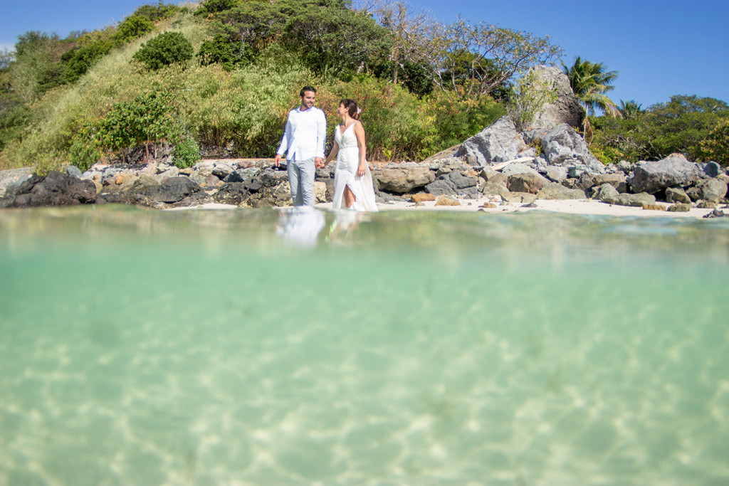 Bride and groom hold hands as they wade through turquoise waters at Castaway