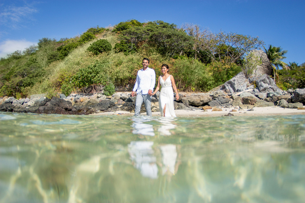 Reflections of the couple as they wade through the clear waters at Castaway Fiji