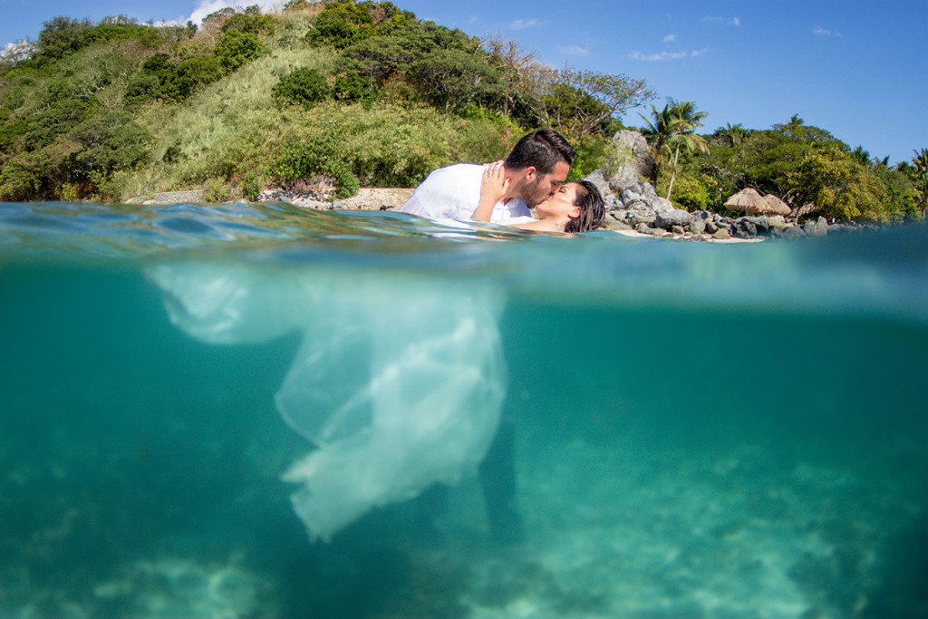 Bride and groom kiss just above water while their bodies are underwater