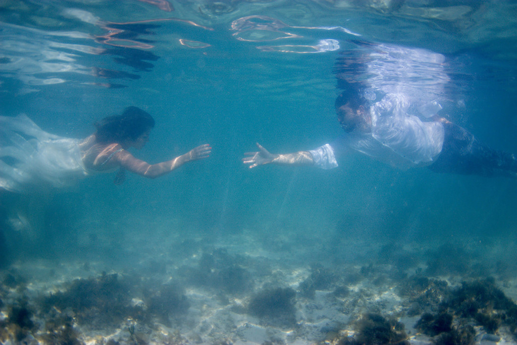 Bride and groom reach out to each other underwater