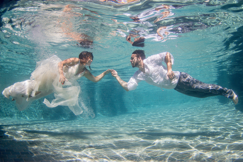Groom reaches out for his magnificent bride underwater