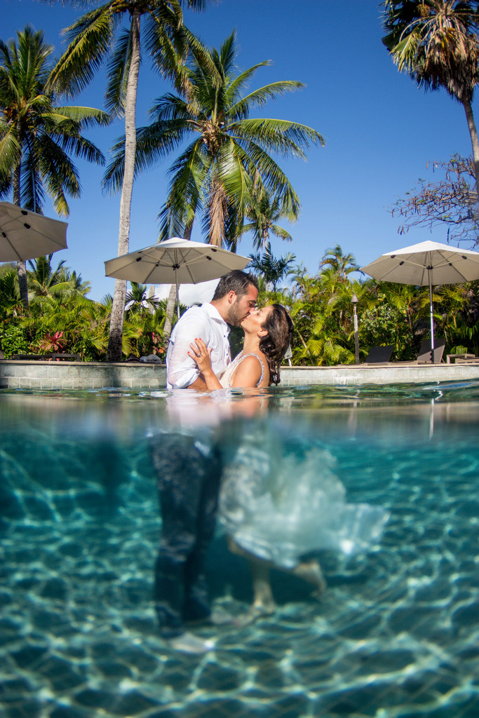 The couple passionately kiss against lofty palm trees while immersed underwater