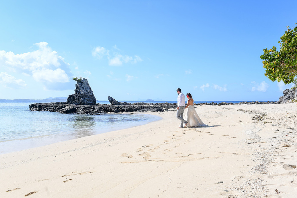 The stunning couple stroll towards the sea at Castaway Fiji reef on a sunny and bright day
