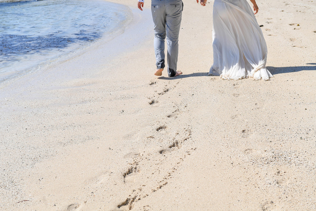 The couple leave footsteps in the sand as they walk towards the sea at their honeymoon