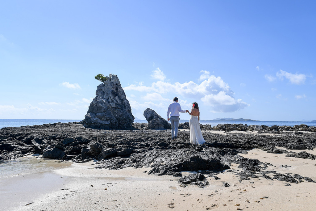 The couple holds hands while standing on the rocks at the Castaway reef against baby blue skies