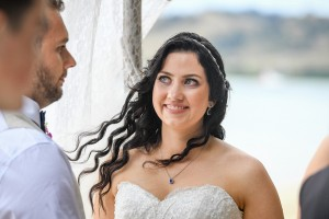 The bride has a big grin as she watches her husband while at the altar