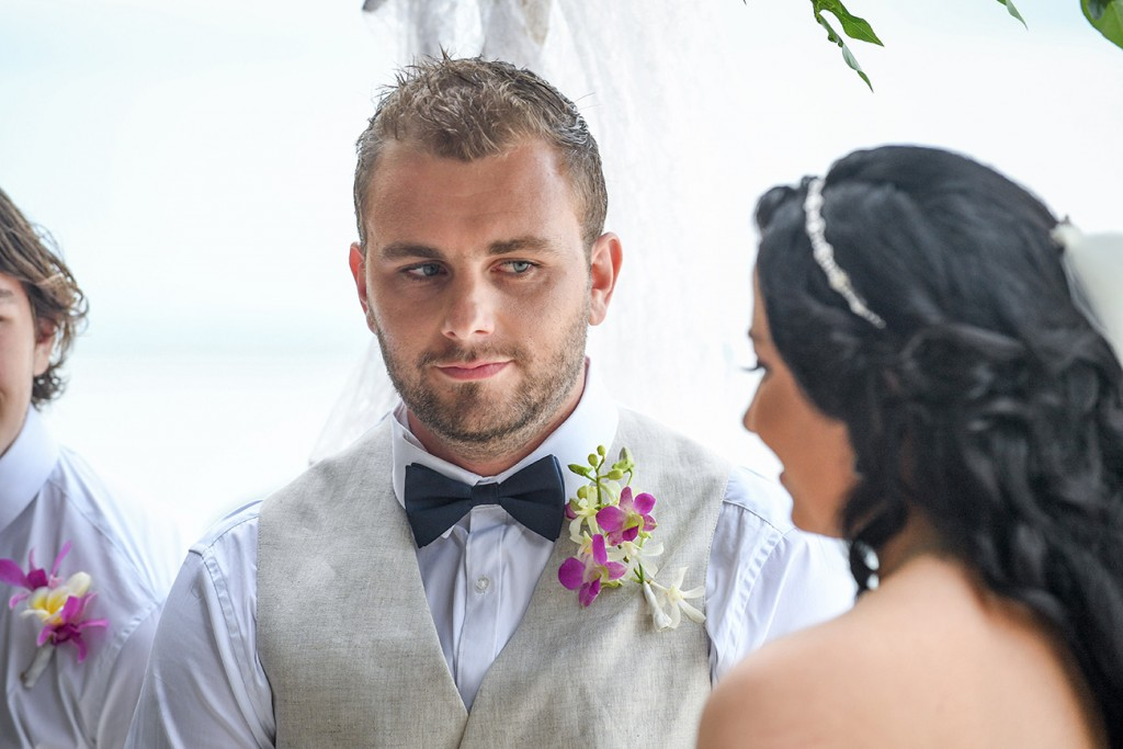 The groom watches keenly as the bride says her vows