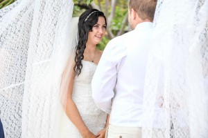 The bride smiles at her groom while at the altar