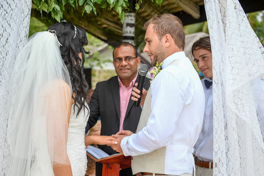 The groom slips the ring onto the bride's finger