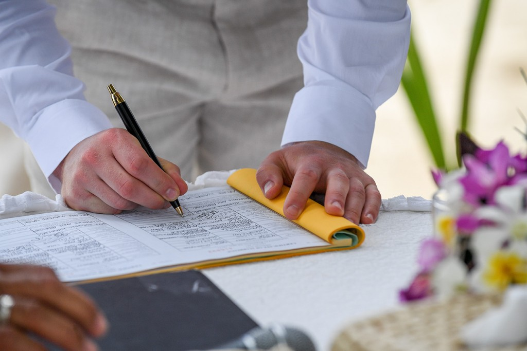 A closeup of the groom signing the marriage certificate