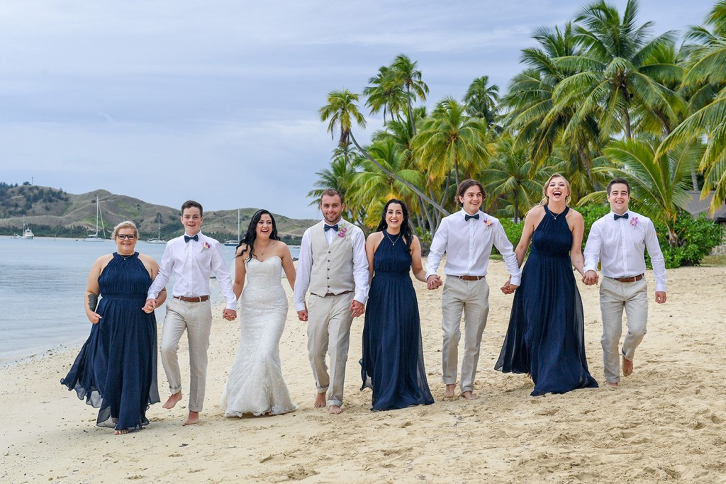 The newly weds pose with the bridal party on the beach at Plantation Island Resort