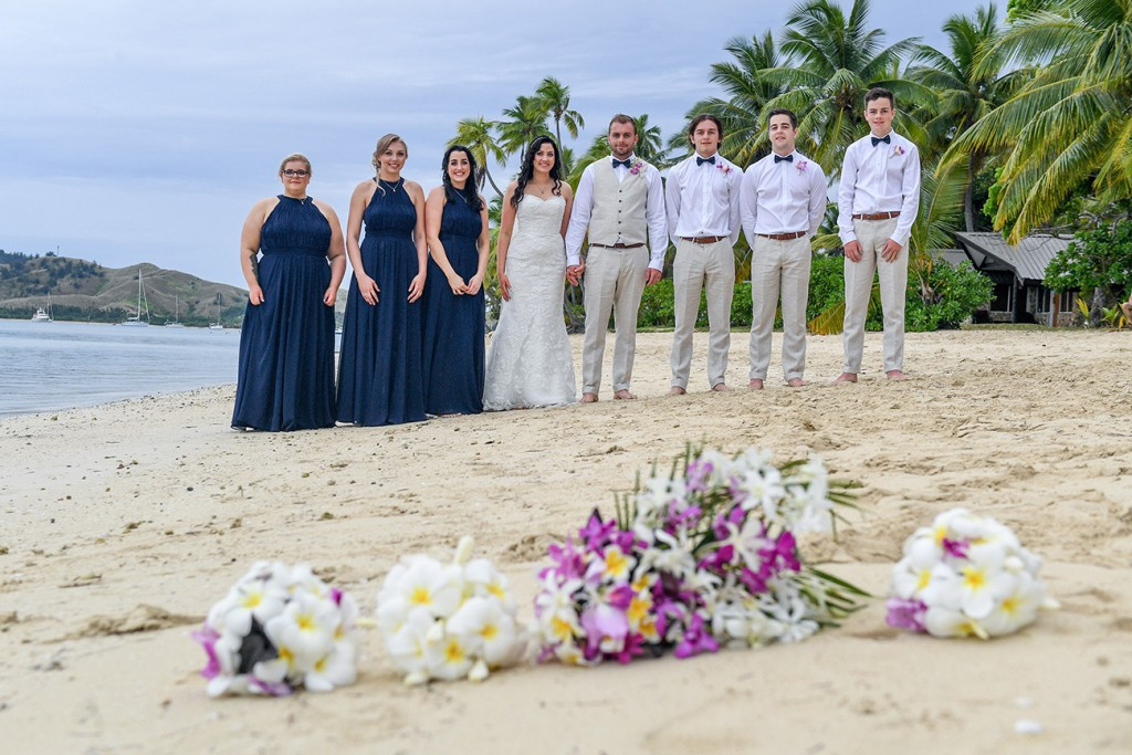 The bridal party poses in front of their flower bouquets