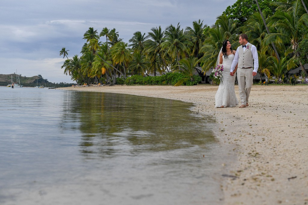 The newly weds stroll along the Plantation Island Resort beach