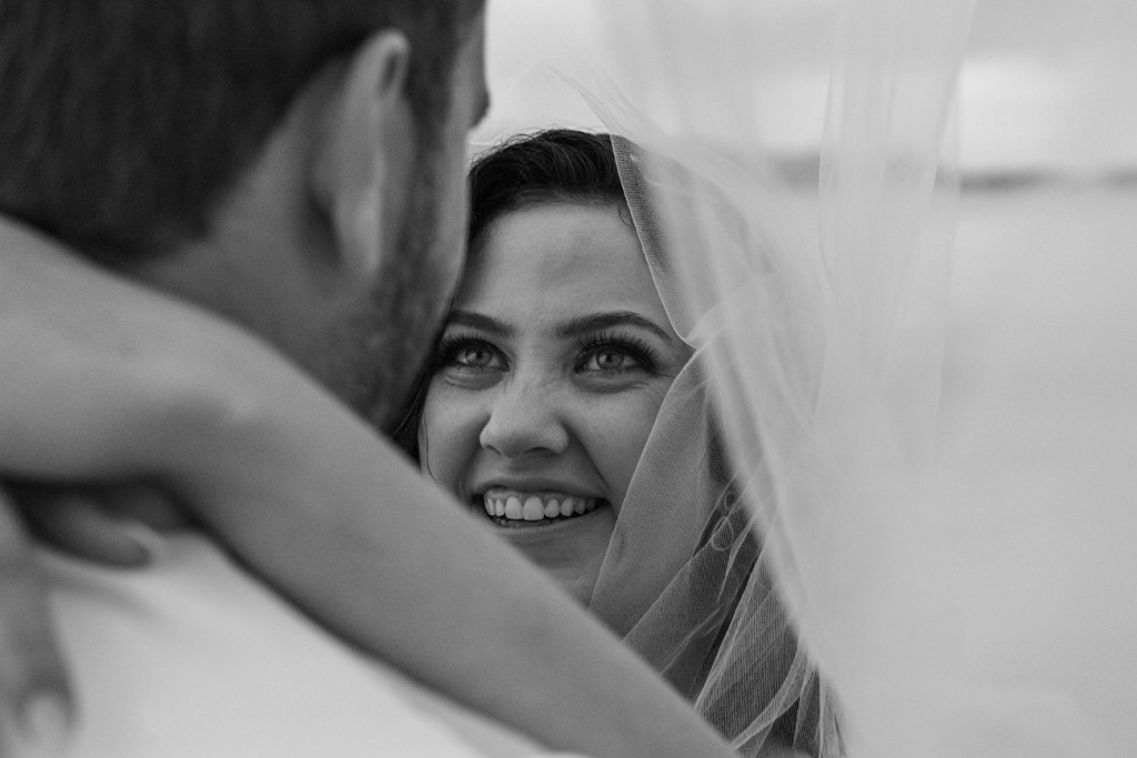 The bride has a gleeful smile under the veil