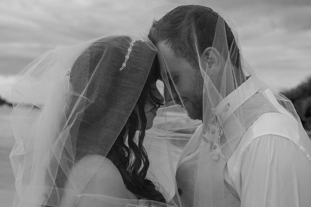 A monochrome photograph of the newly weds being intimate under the veil