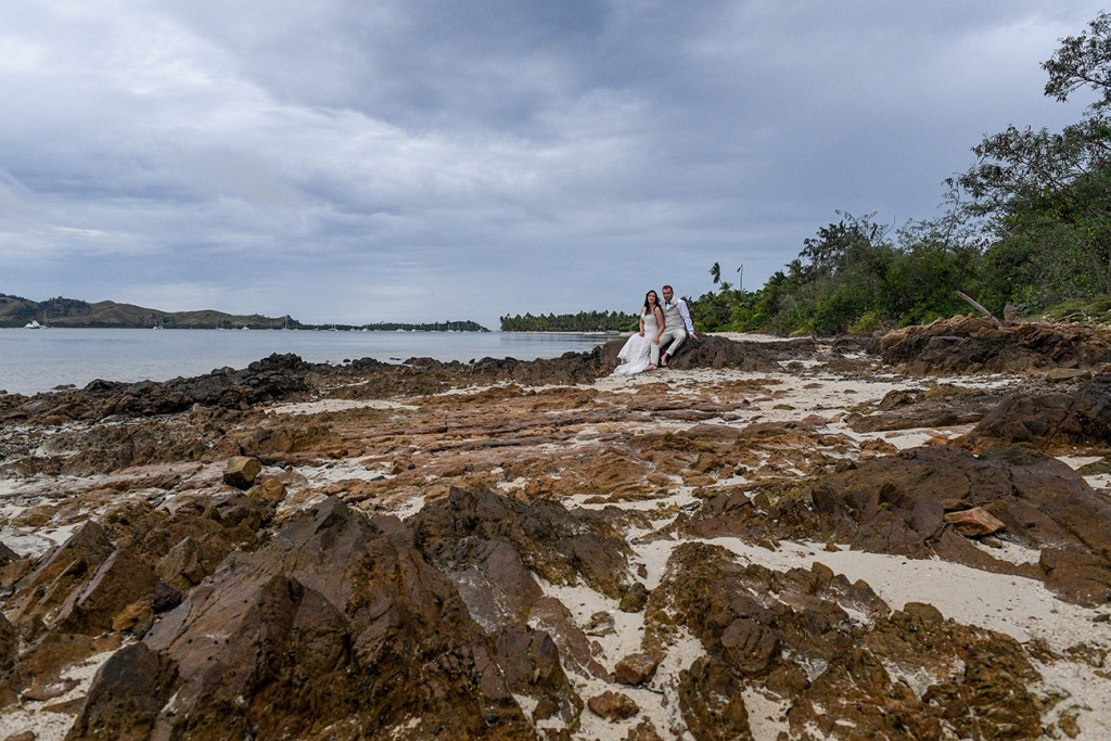 The newly weds pose on beach rocks at Plantation Island Resort Fiji