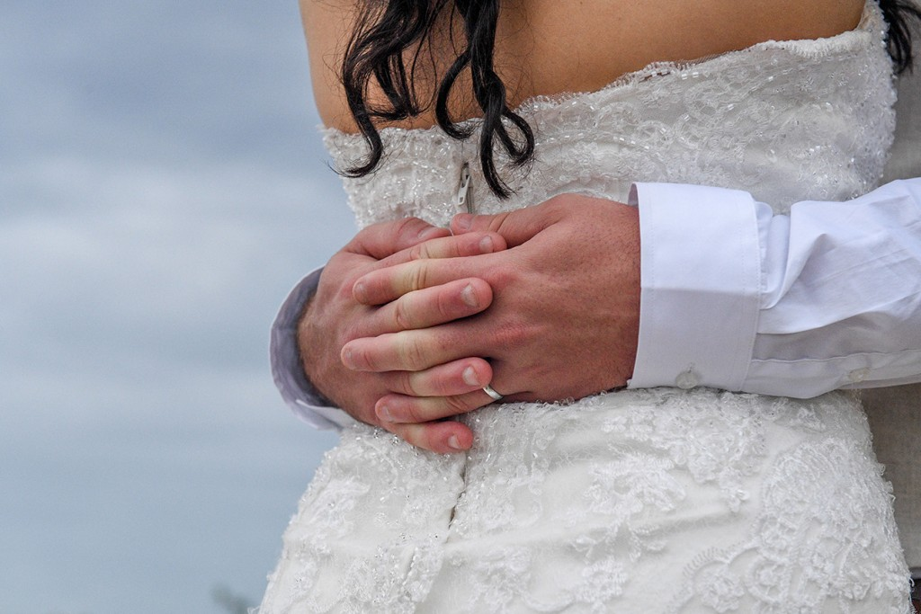 Groom's hands behind bride's back