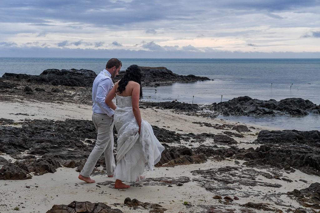 The newly weds walk on rocky beach to pose for their photos