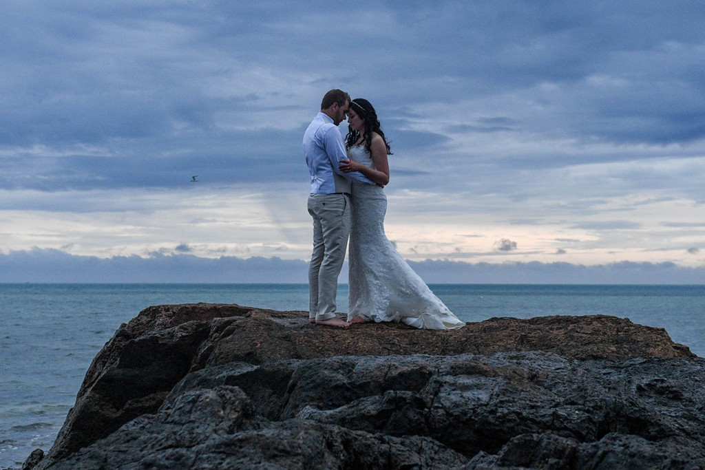 The newly weds share an intimate moment atop a rock against a glum sunset