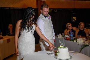The newly weds cut their wedding cake together