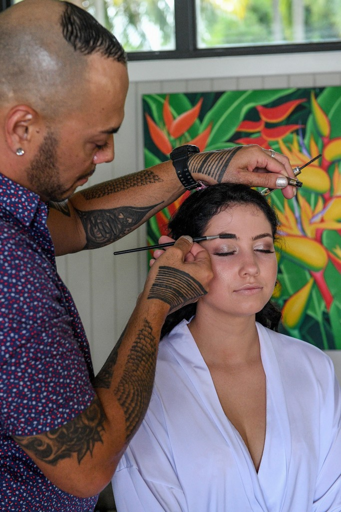 The makeup artist touches up a bridesmaid's eyebrow