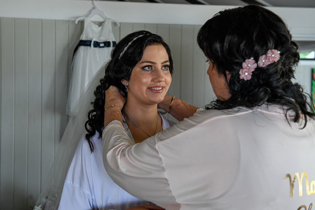 The bride smiles as her necklace is put on her