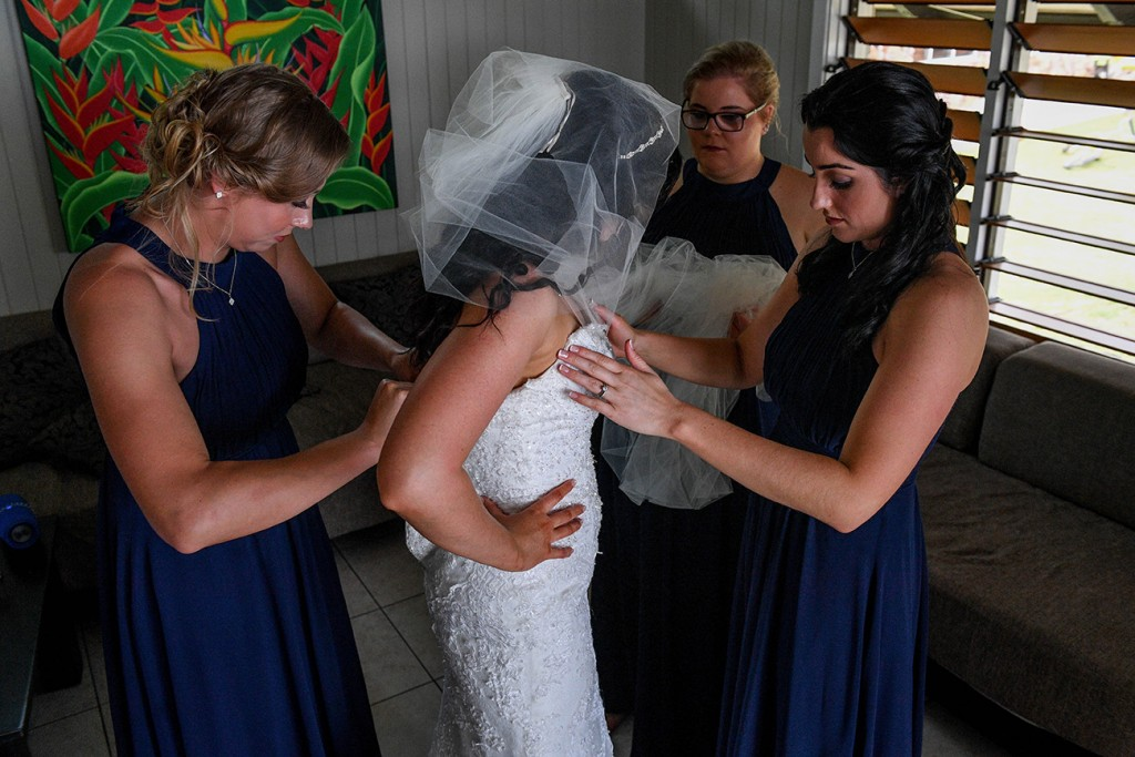 The bridesmaids help the bride fit into her wedding dress