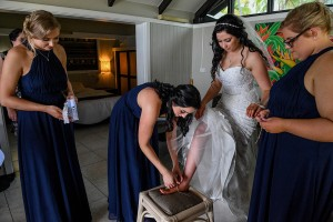 A bridesmaid helps the bride where her wedding sandals
