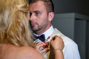 A bridesmaid helps the groom pin the flower boutonniere on the groom
