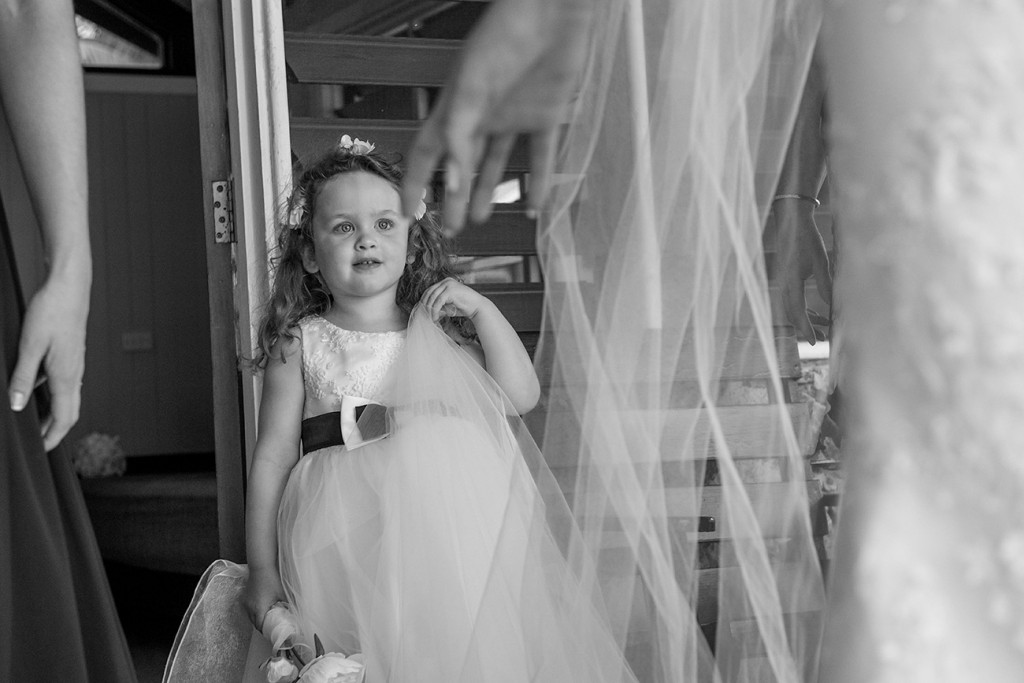 A peek of the flower girl through the veil